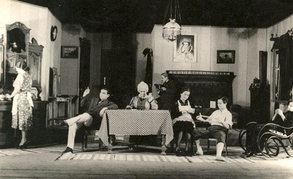 """Teatrul Popular Românesc din Vârșeț – o scenă din """"Titanic vals"""" – actul întâi – fotografie păstrată de dl Ursulescu """"În stagiunea 1951/52 a fost pusă în scenă piesa """"Titanic vals"""" de Victor Eftimiu – ne mărturisește dl Miu Ursulescu.  În fotografie se poate vedea o scenă din actul întâi în care au fost surprinși pe peliculă următorii actori: (de la stânga): Lili Bocșan, E. Ursulescu, Mara Isaia, Iconia Cuzma, Aurelia Pitic (Imbroane, Bugariu) și Cornelia Ilia"""""""